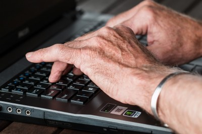 elderly hands on laptop